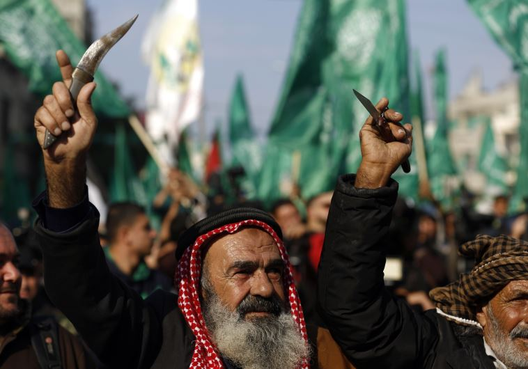 Palestinians carry knives and daggers as they attend a military parade of members of al-Qassam Brigades, the armed wing of the Hamas movement, to mark the 28th anniversary. (photo credit:MOHAMMED ABED / AFP)