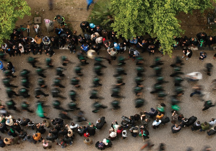 PEOPLE WATCH as Palestinian members of al-Qassam Brigades parade in Gaza. (photo credit:REUTERS)
