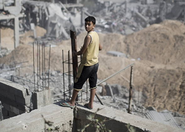 A Palestinian youth looks out at the destruction in part of Gaza City's al-Tufah neighborhood on Wednesday during the cease-fire. Photo by Mahmud Hams/AFP/Getty Images