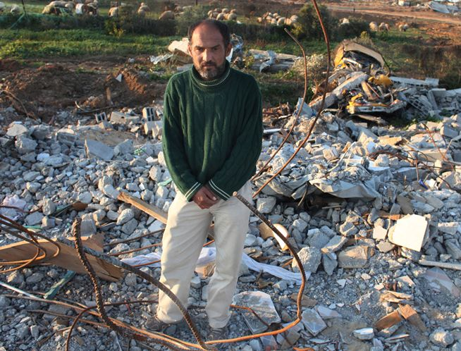 Raid el Atmnah, 37, stands in rubble that used to be his home in Gaza. He was ordered to leave and returned to find the rubble.