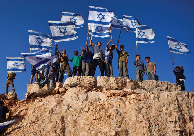 Jewish Youths in Israel wave flags and stand atop a hill. The author recalls his own young days in Zionist youth groups