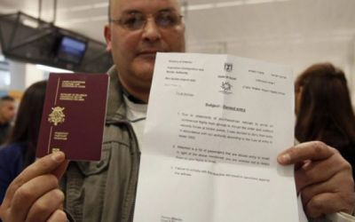 A would-be passenger posing with his passport and a letter denying him access to Israel as around 100 pro-Palestinian activists stage a protest at Brussels national airport April 15, 2012.