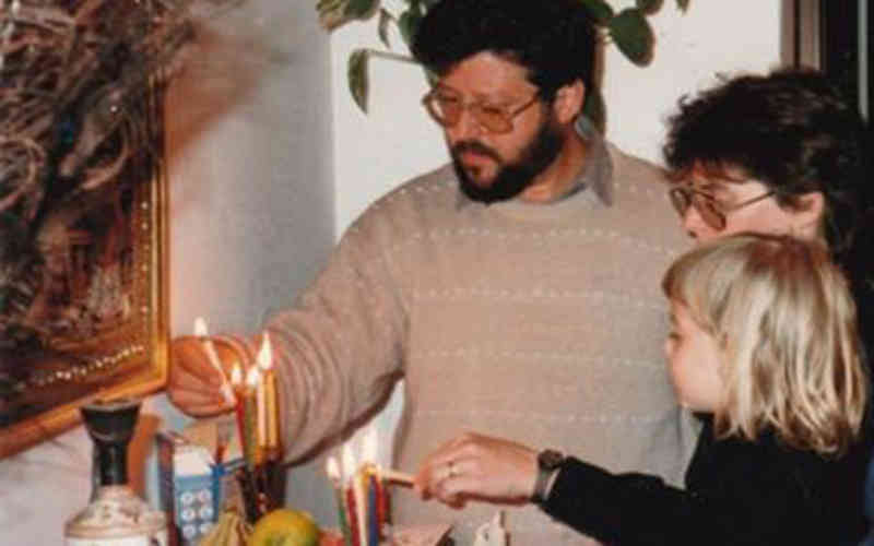 Gershon Baskin, Michal Schonbrun and Elisha Baskin lighting Hanukkah Candles