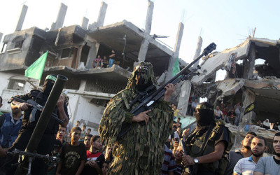 Hamas militants display weapons in front of a destroyed house east of Gaza City, Aug. 27, 2014. (photo by REUTERS/Majdi Fathi)