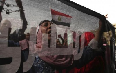 A protester who opposes Egyptian President Mohamed Mursi, is seen through a flag, on which the word Egyptian is inscribed, as she chants slogans during a demonstration against Mursi and members of the Muslim Brotherhood at Tahrir Square in Cairo,