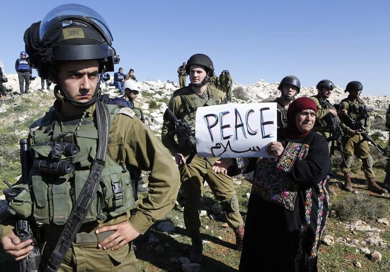 Palestinian protest in West Bank A protester holds a placard as she stands next to Israeli soldiers during a protest against Israeli settlements in Beit Fajjar town south of the West Bank city of Bethlehem. (photo credit:REUTERS)