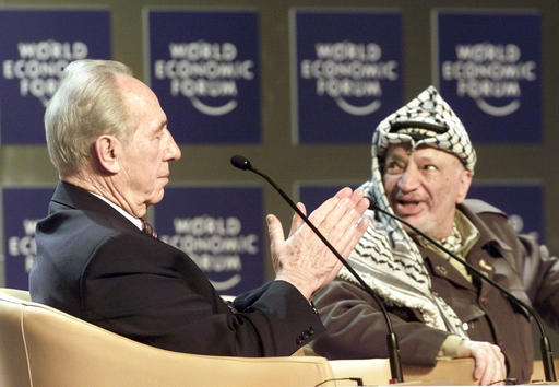 """Shimon Peres, Minister of Regional Cooperation of Israel, left, applauds Palestinian leader Yasser Arafat, right, as it is announced that Arafat is about to speak at the Davos World Economic Forum. Both took part in the forum on """"From Peacemaking to Peacebuilding."""" Peres, a former Israeli president and prime minister, whose life story mirrored that of the Jewish state and who was celebrated around the world as a Nobel prize-winning visionary who pushed his country toward peace. (AP Photo/Herbert Knosowski)"""