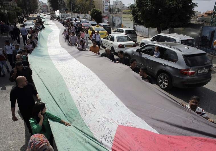 PEOPLE MARCH as they hold a large Palestinian flag in Ramallah in October.