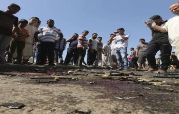 Gaza Palestinians survey the wreckage of an IAF strike that killed two terrorists in Gaza. Photo: REUTERS